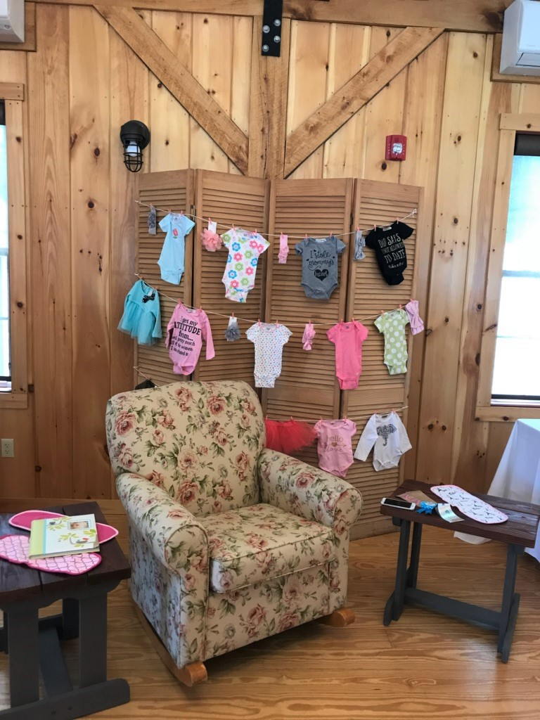 The 228 decorated for a baby shower with onesies hung on strings behind the armchair