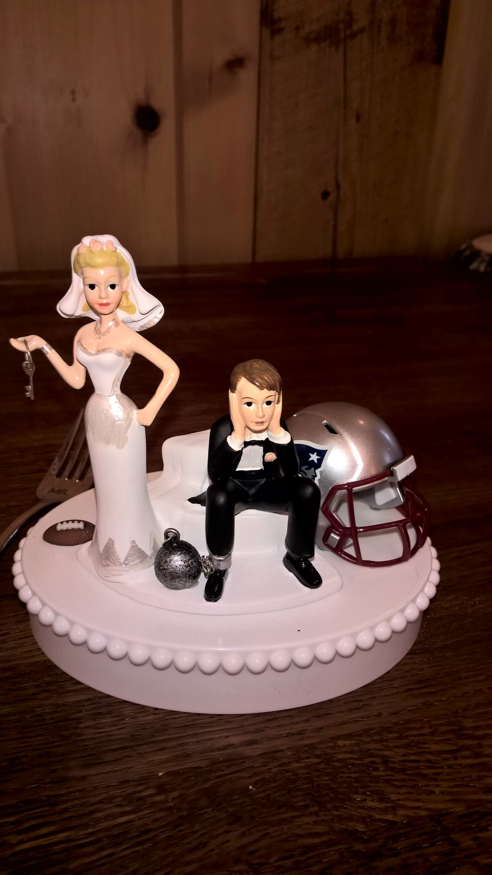 Cake topper with bride and unhappy groom with ball and chain on his ankle.