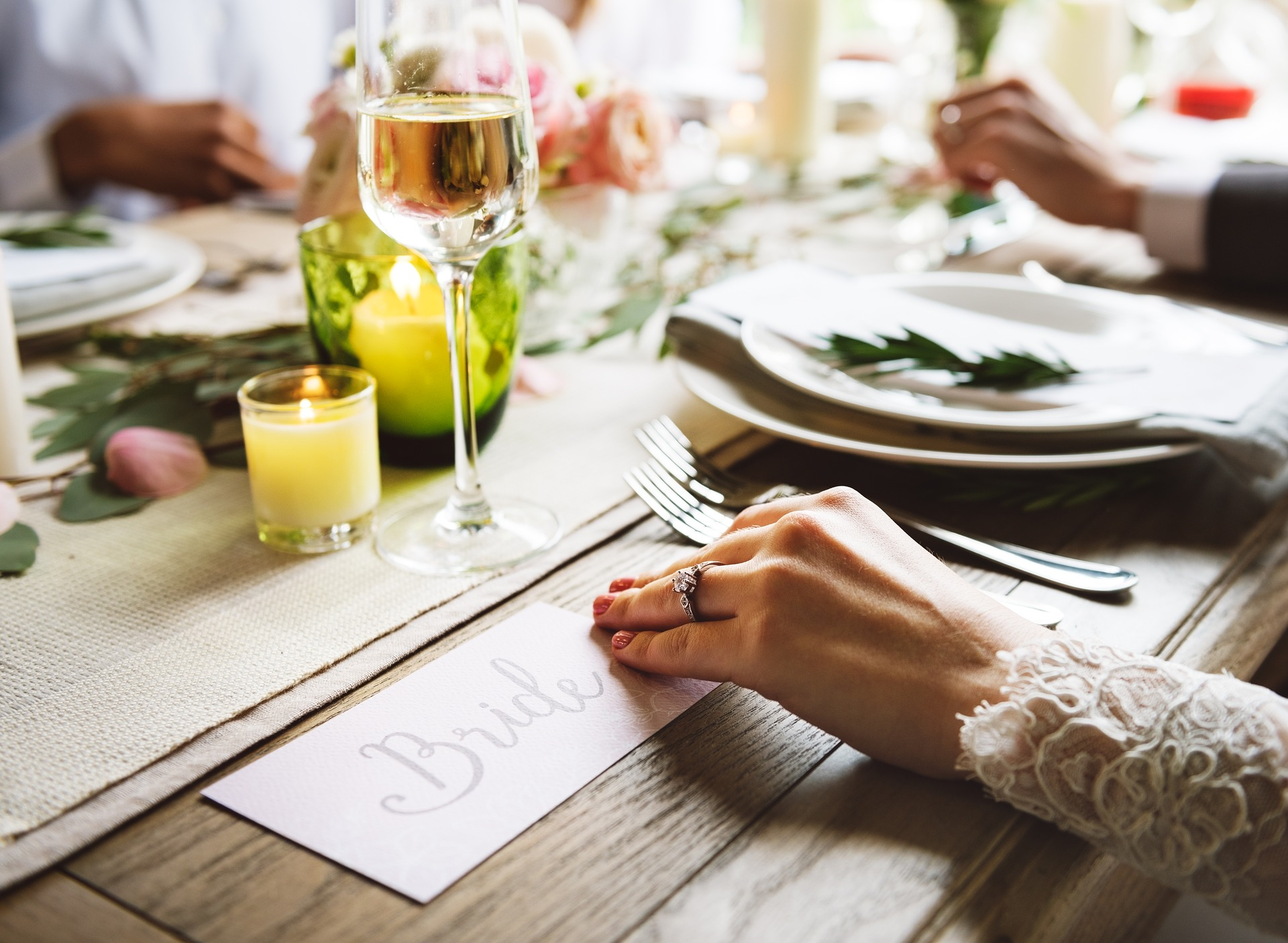 """part of table at wedding reception showing """"bride"""" place and her hand as well as plates, wine glass, and candle"""