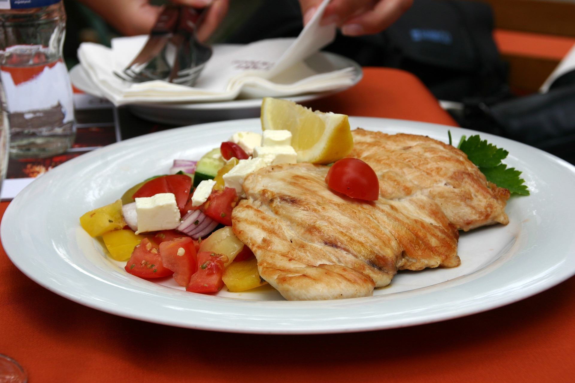 plate with chicken and a tomato feta salad