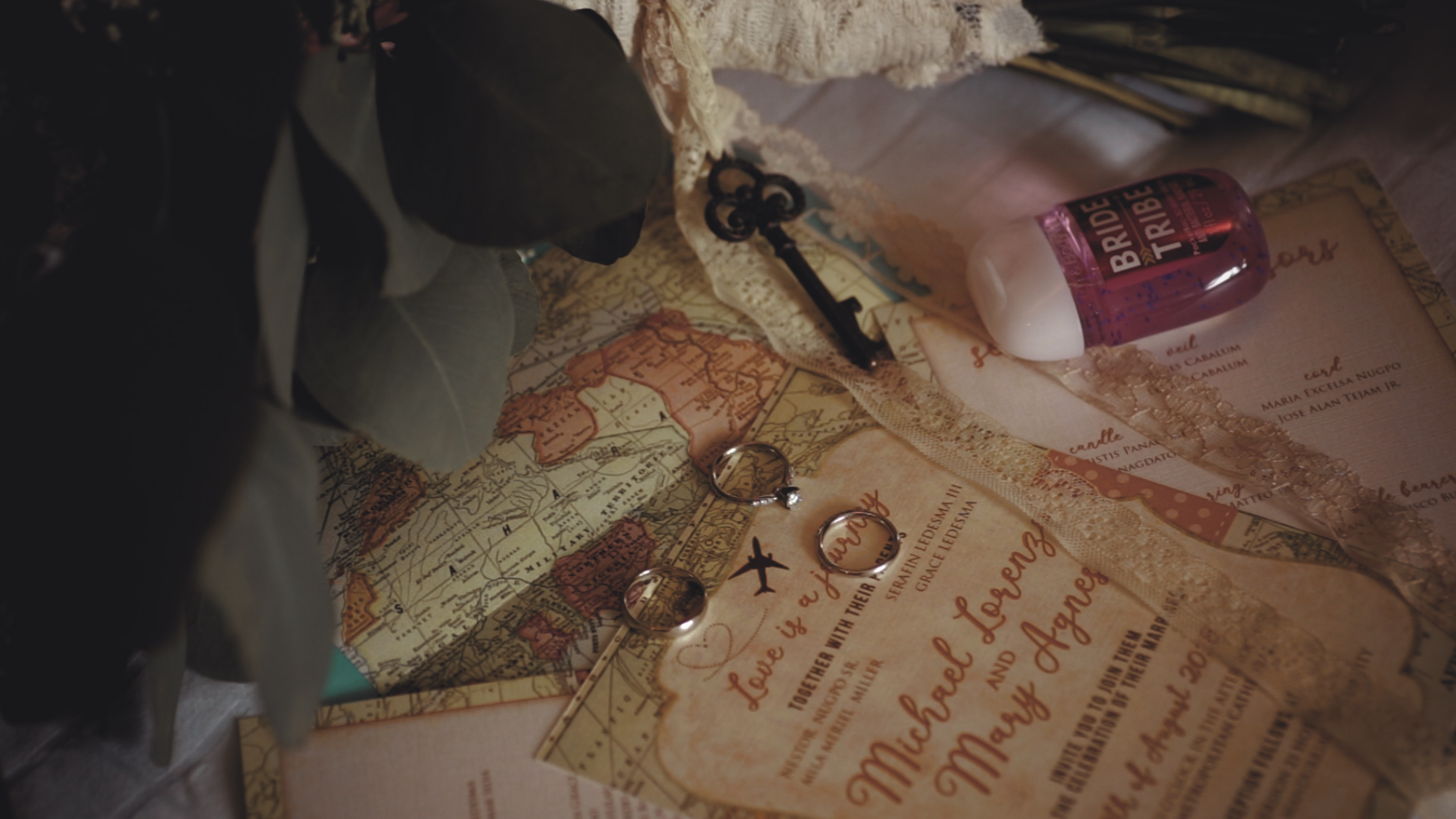 travel-themed wedding invitation and rings on top of a map