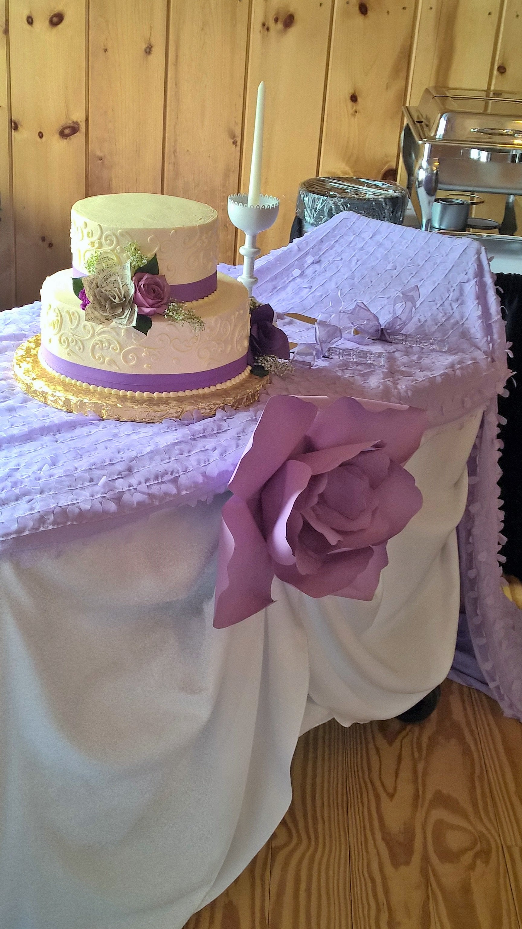 wedding cake on table decorated with purple and white clothes and a large paper purple flower