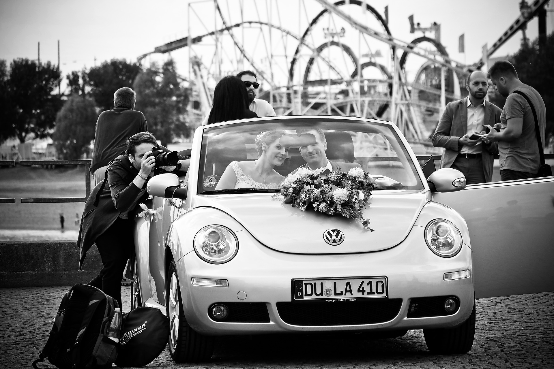 just married couple in decorated car while photographer takes wedding photos of them