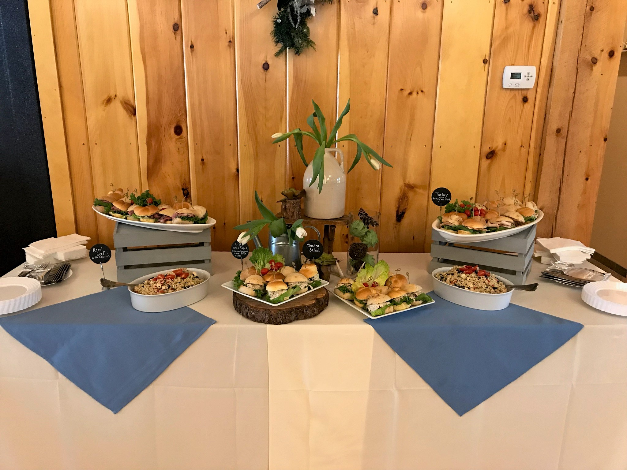 An assortment of dishes on a table with a white tablecloth and blue napkins. Using appetizers instead of a sit-down meal can cut catering costs.