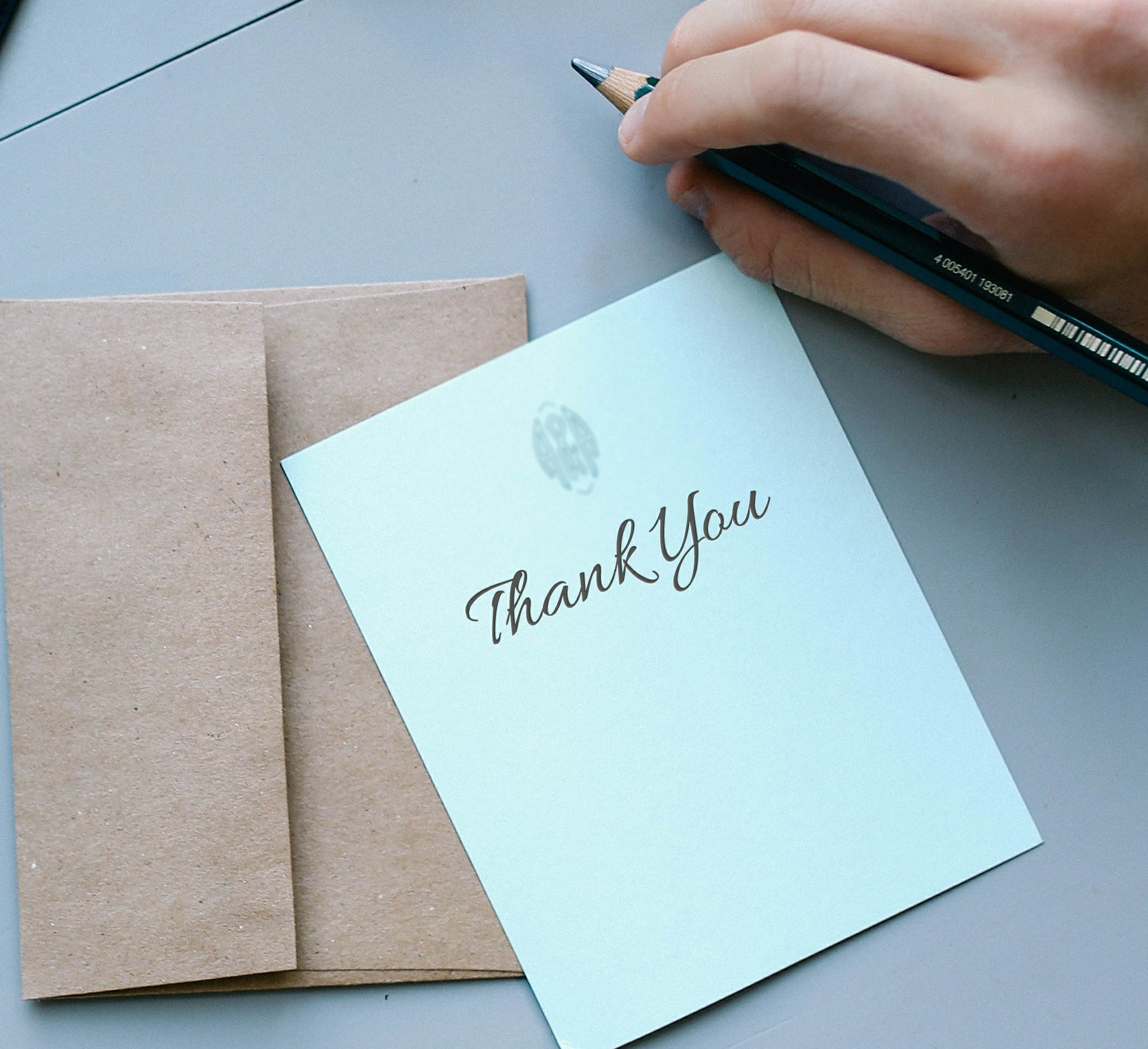 thank you card and envelope next to hand holding a pen