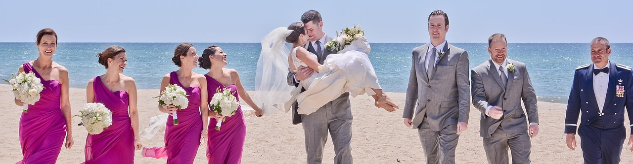 groom carrying bride with groomsmen, and bridesmaids walking along beach