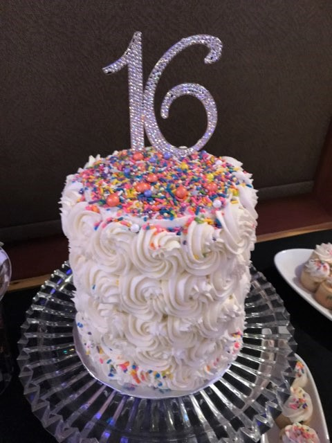 sweet 16 birthday cake with white frosting, sprinkles, and a silver glitter 16 on top