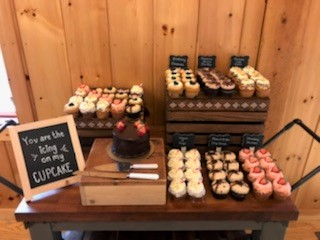 an example of food stations: table with display of various cupcakes
