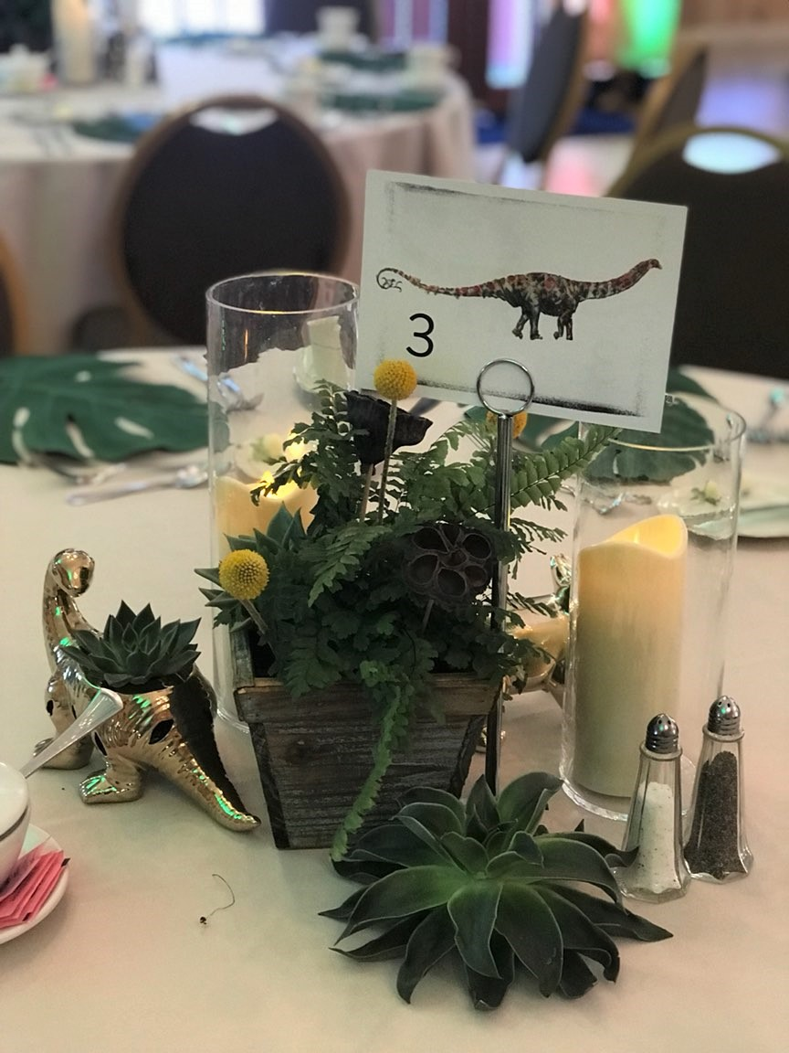centerpiece with greenery candle, dinosaur toy, and a dinosaur card with the table number