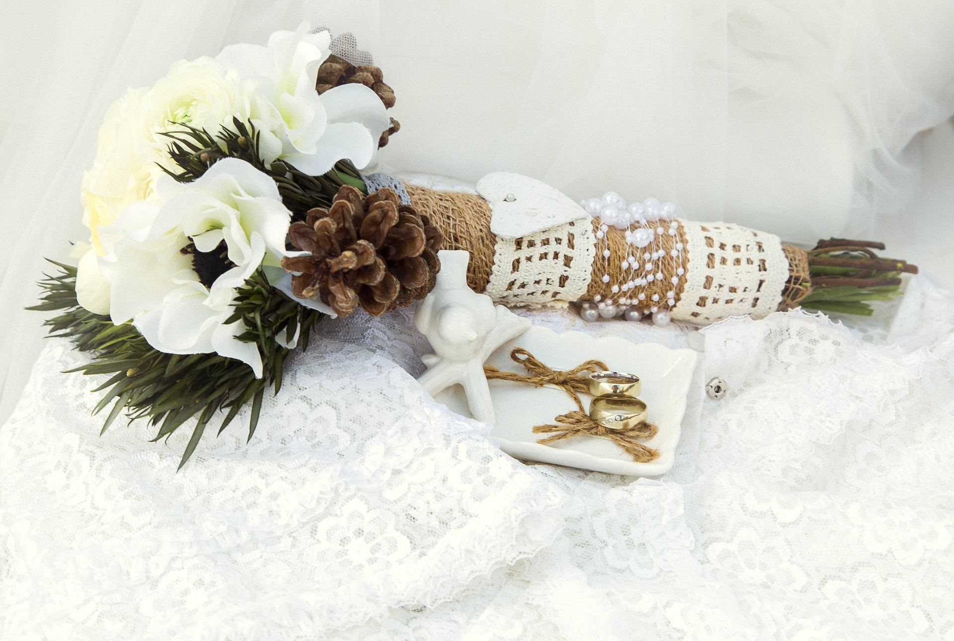 Winter wedding bouquet with pine, pine cones, and white flowers wrapped in lace and burlap