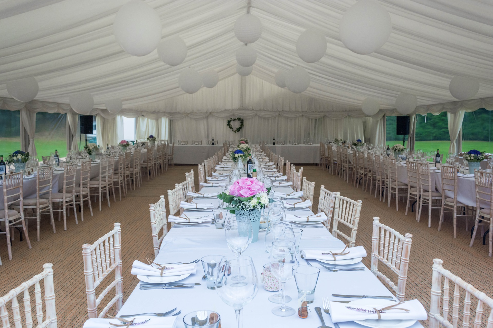 view of inside of a white tent with long tables set up for wedding reception.